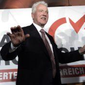 Frank Stronach vor einem Wahlplakat